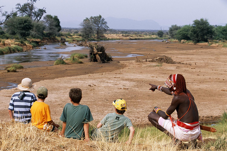 Kenya, Samburu. A Samburu warrior talks to children about the bush on a Cheli & Peacock family safari.